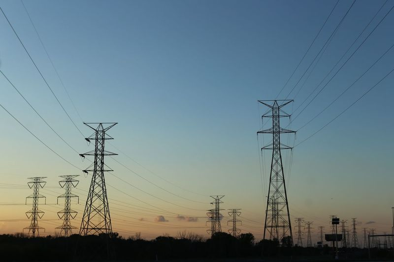 Electricity Pylons Against Sky