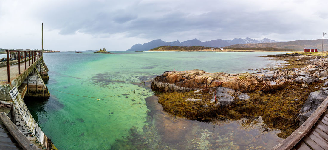 landscape view of Senja Island in Norway Barents Sea, Northern, Senja Island, Arctic, Atlantic, Coast, Cold, Europe, Fishing, Fjord, Harbor, Holiday, Ice, Landscape, Mountains, Nature, Nordic, North, North Sea, Norway, Norwegian, Ocean, Outdoor, Polar Circle, Port, Scandinavia, Sea, Seascape, Sky, Spring, Summer, Tourism, Travel, Village, Water Water Sky Cloud - Sky Sea Nature Scenics - Nature Beauty In Nature Tranquility Day Tranquil Scene Transportation No People Beach Nautical Vessel Mountain Land Outdoors Built Structure Non-urban Scene Turquoise Colored