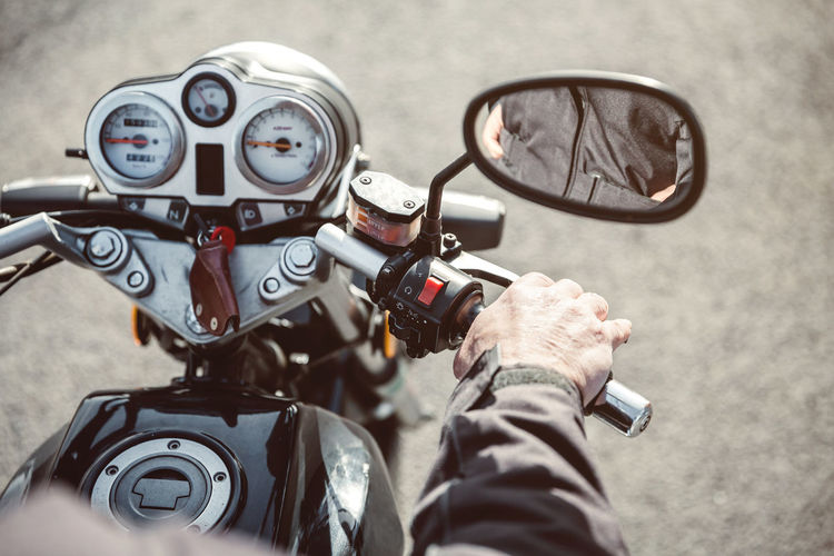 Close up of senior man hand steering motorcycle on the road Asphalt Hands Horizontal Man Mirror Motorcycle Motorcyclist Retro Road Transportation Travel Wheel Adventure Bike Close Up Male Motorbike One Person Ride Route Senior Steering Vehicle Vintage Way