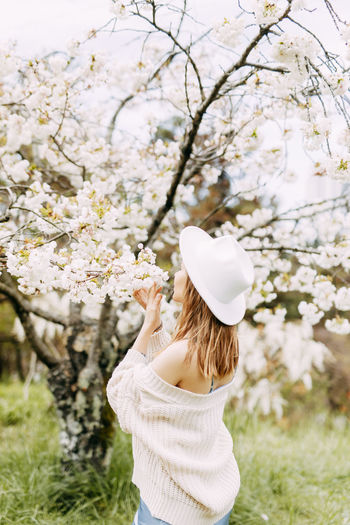 Gentle girl in a dress and a fashionable hat is walking enjoying the smell of flowers in the park