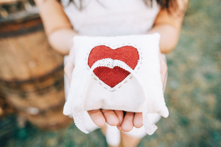 Close-up of woman holding heart shape pillow