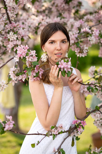 Portrait of woman with pink flower against plants