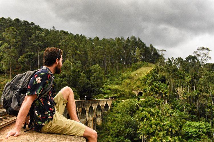 Man sitting on railway bridge against mountain