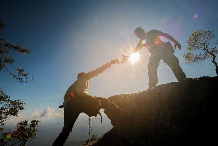 Man helping to climb the rock Adventure Enjoyment Extream Helping Hand Human Arm Human Hand Leisure Activity Lens Flare Men Nature Outdoors People Positive Emotion Sky Sun Sunbeam Sunlight Sunset Togetherness Two People