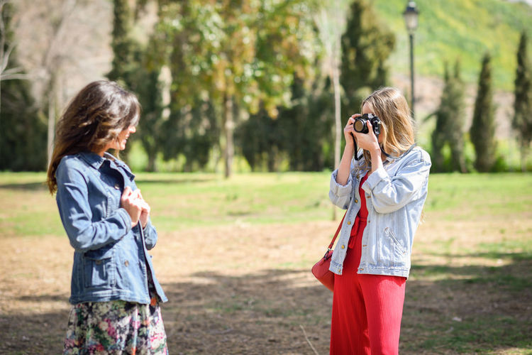 Woman photographing smiling friend in park during sunny day