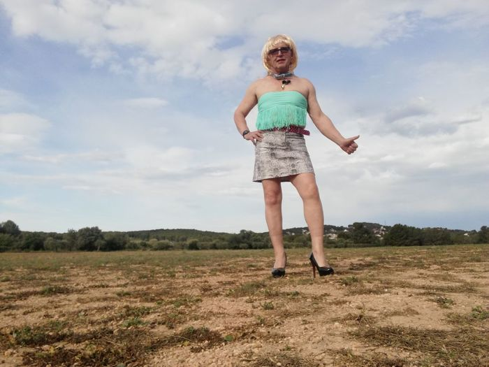 Full length portrait of woman gesturing while standing on grass against sky