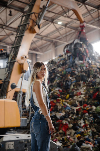 Portrait of young woman standing against garbage heap