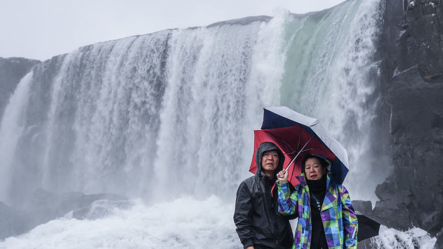 Portrait of couple standing against waterfall