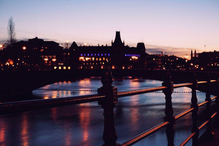 Bridge over river in city at dusk