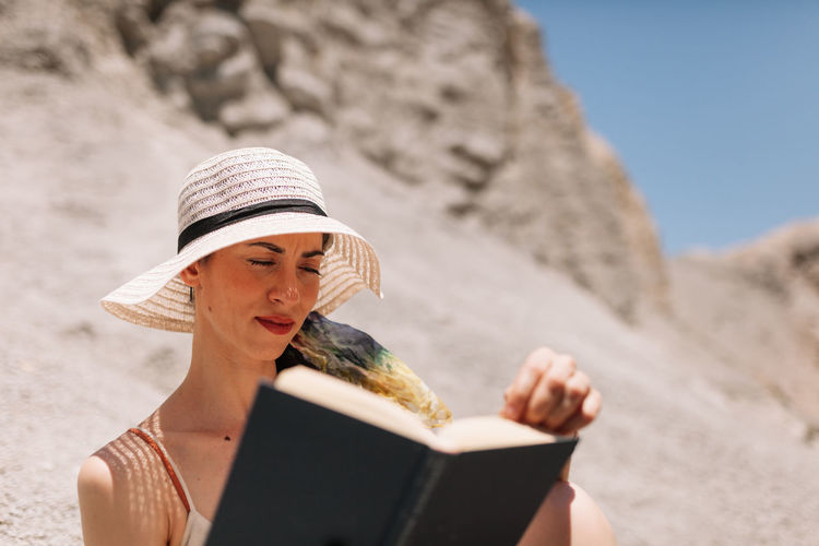 Midsection of woman reading book on beach