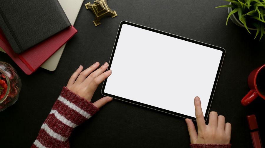 Cropped hands using digital tablet at desk