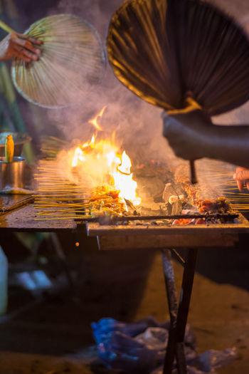 Cropped image of men preparing satay at market stall