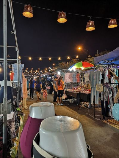 People at illuminated market stall at night