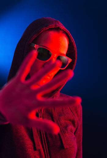 Close-up portrait of woman wearing sunglasses against blue background