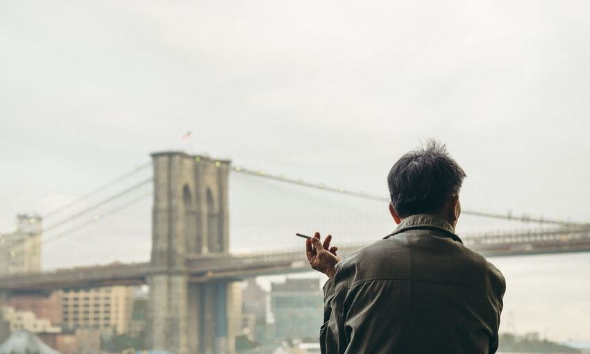 Rear view of man holding cigarette against brooklyn bridge