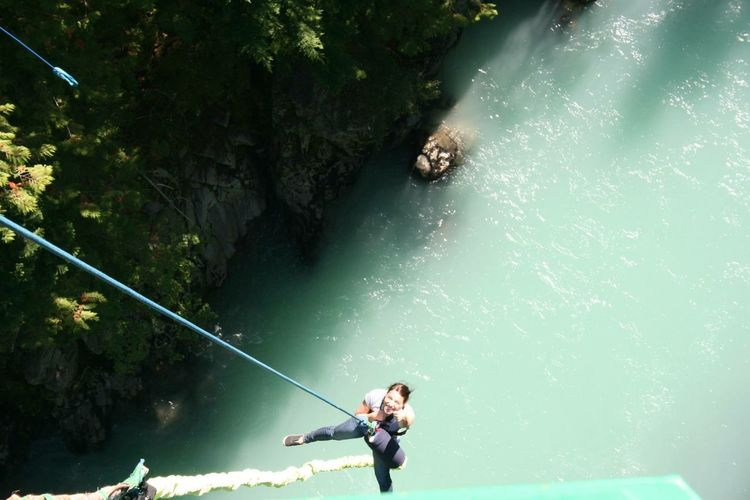 High angle view of woman skydiving over river in forest