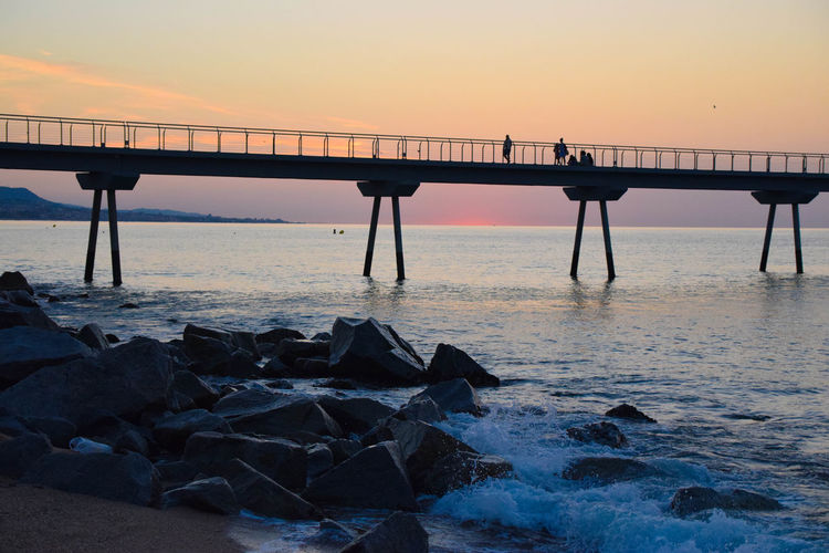 First walk of the day Architectural Column Beach Beauty In Nature Bridge Bridge - Man Made Structure Built Structure Horizon Horizon Over Water Land Nature Orange Color Outdoors Rock Scenics - Nature Sea Silhouette Sky Solid Tranquil Scene Tranquility Water