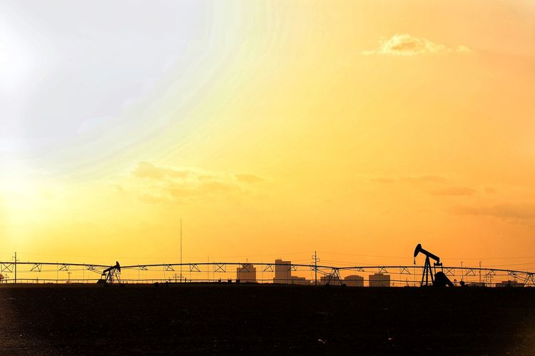 Summer heat with silhouette of pump jacks and city Desert Drought Energy Agriculture Petroleum Products Texas Solar Fossil Fuel Oil Production Permian Basin Oil Industry Midland, TX Oil And Gas Industry Desert Heat Texas Skies Texas Energy Sky Sunset Silhouette Orange Color Nature Beauty In Nature Cloud - Sky Scenics - Nature Sunlight Land Architecture Built Structure Outdoors