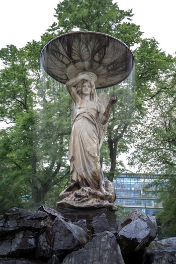 Low angle view of statue against trees in park