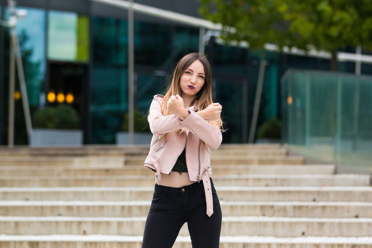 Portrait of young woman clenching fists on steps