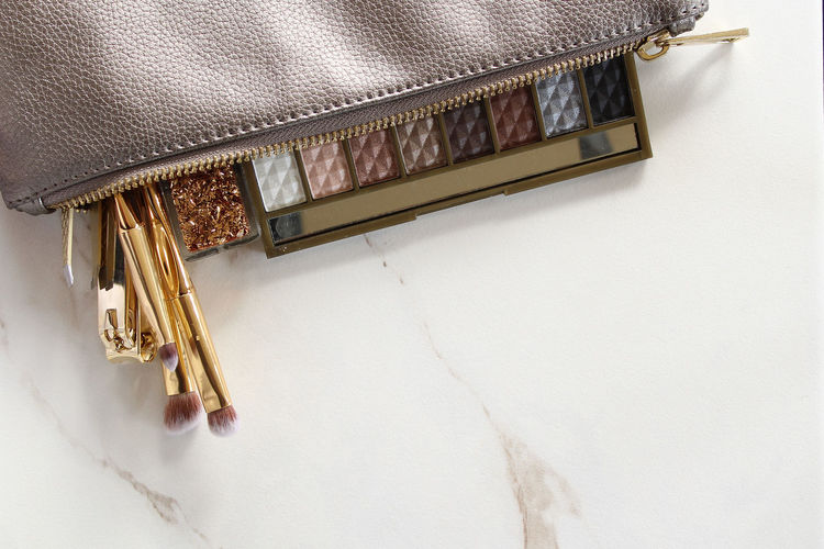 High Angle View Of Make-Up Brushes In Purse On Marble