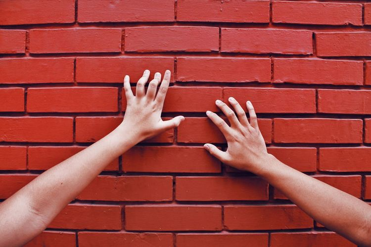 Cropped Image Of Women Touching Brick Wall