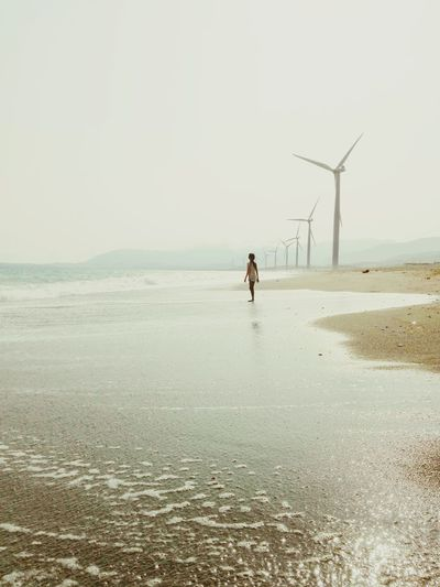 Girl standing on shore at beach with wind turbines against sky