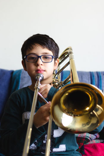 Portrait of cute boy holding trumpet while sitting on sofa at home