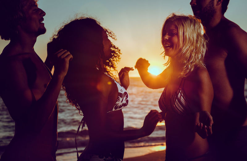 Friends dancing at beach against sky during sunset