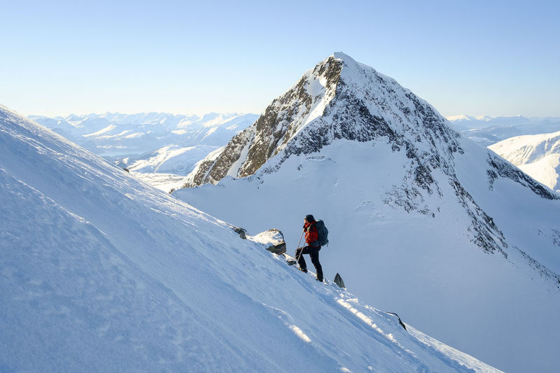 Woman hiking on snowcapped mountain against clear sky