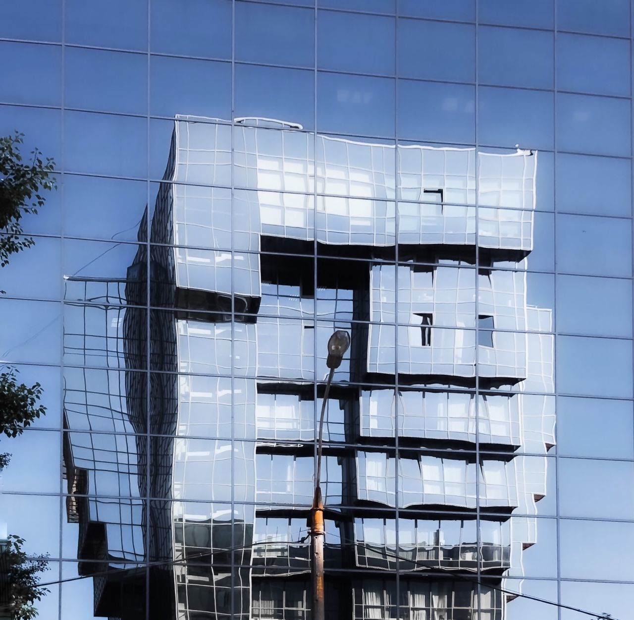 LOW ANGLE VIEW OF OFFICE BUILDING IN GLASS