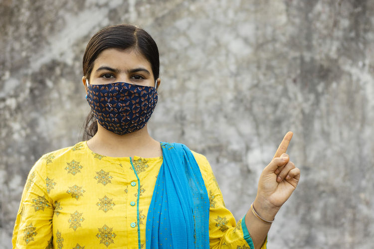 An indian woman wearing homemade cotton nose mask, looking at camera and pointing left side