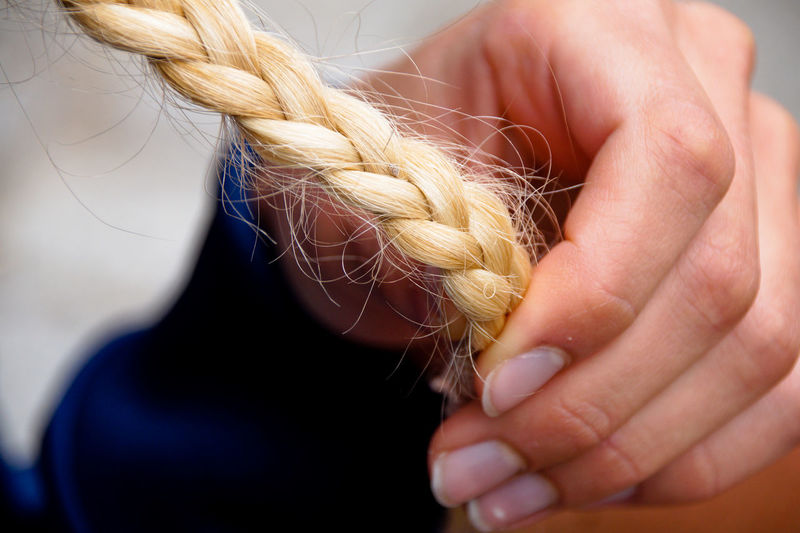 Cropped Image Of Hand Holding Braided Hair