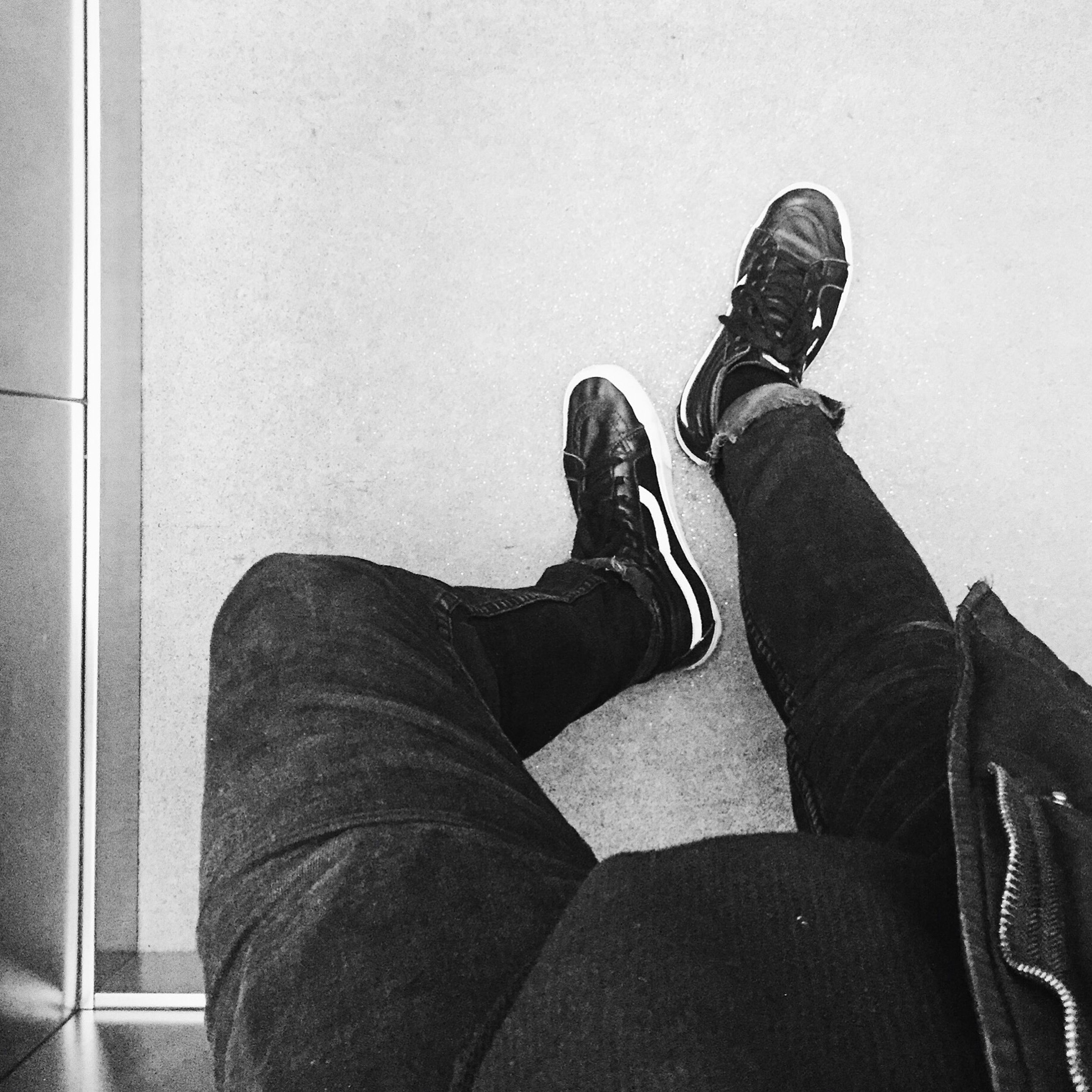 low section, person, shoe, personal perspective, lifestyles, standing, men, human foot, indoors, footwear, jeans, leisure activity, legs crossed at ankle, wall - building feature, high angle view, unrecognizable person