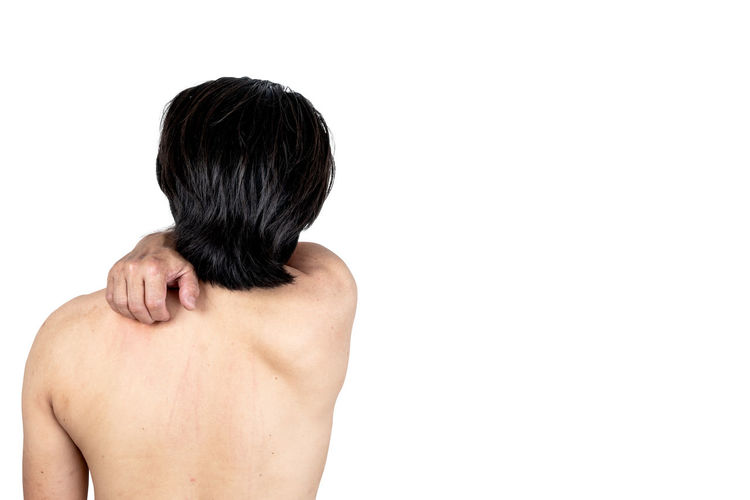 Rear view of shirtless man against white background