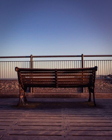 Empty bench by railing against clear blue sky