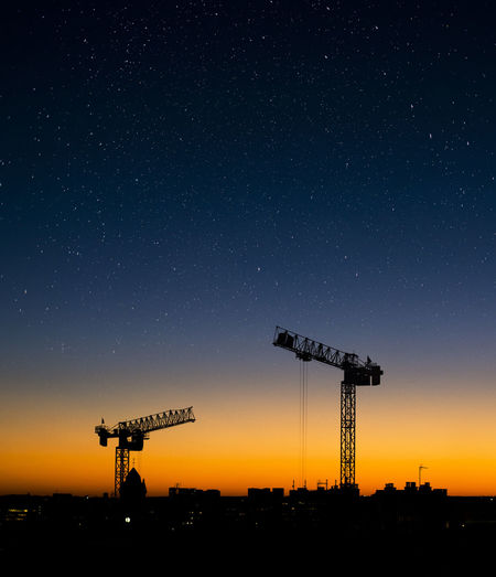 Cranes against sky at night