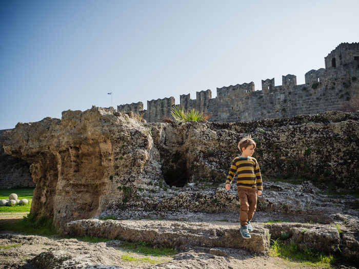 Boy looking away while walking against built structure and clear sky