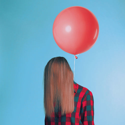 Woman with balloon standing against blue wall