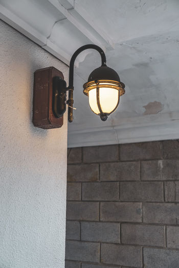 Low angle view of light bulb on wall