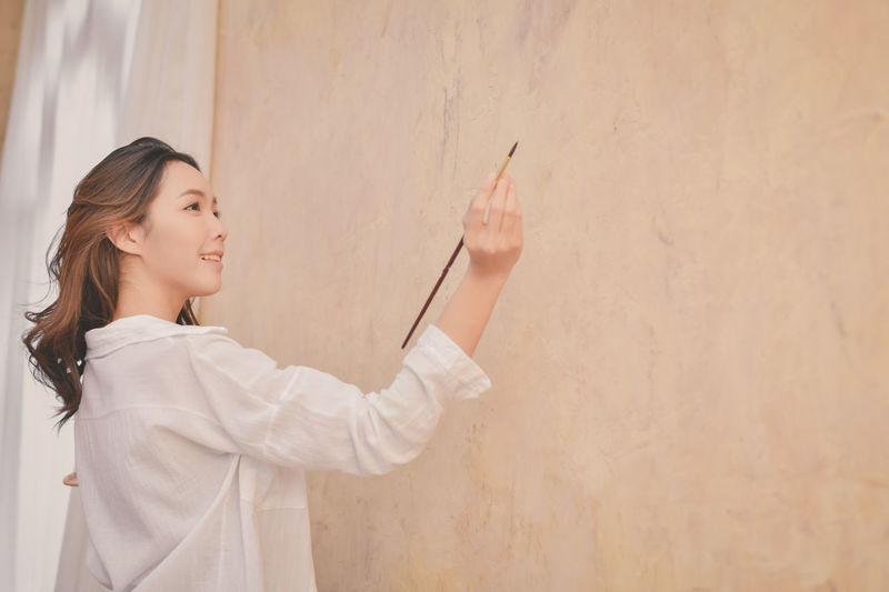 Young painter painting on wall at home