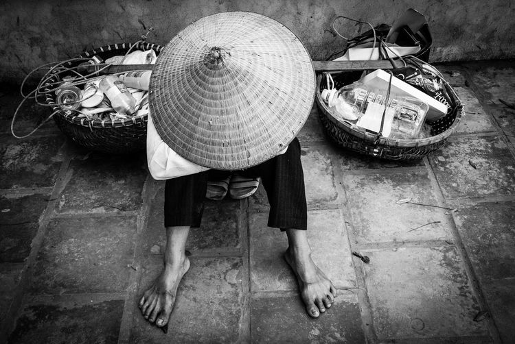 Man wearing asian style conical hat while sitting at market
