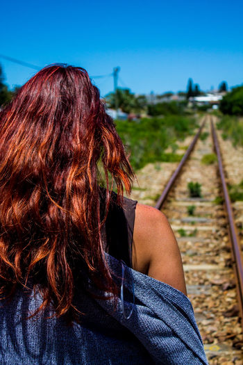 Rear view of woman with railroad tracks against sky