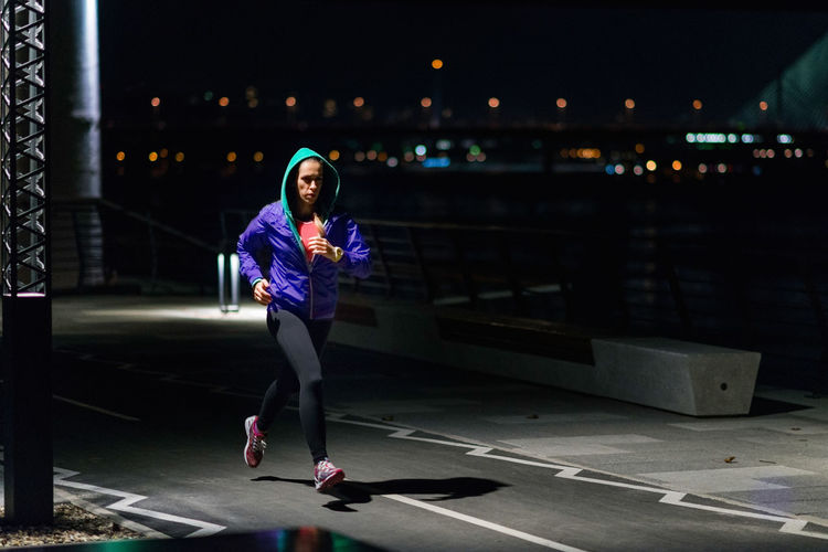 Full Length Of Woman Running On Road At Night