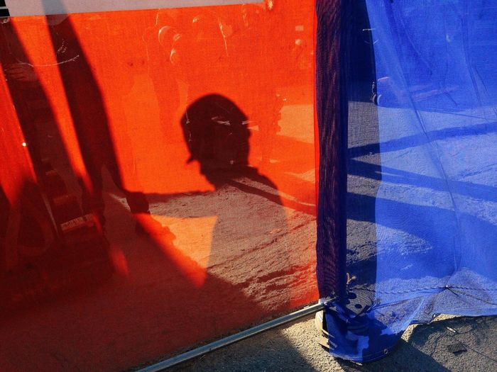 Shadow of worker on red textile at construction site