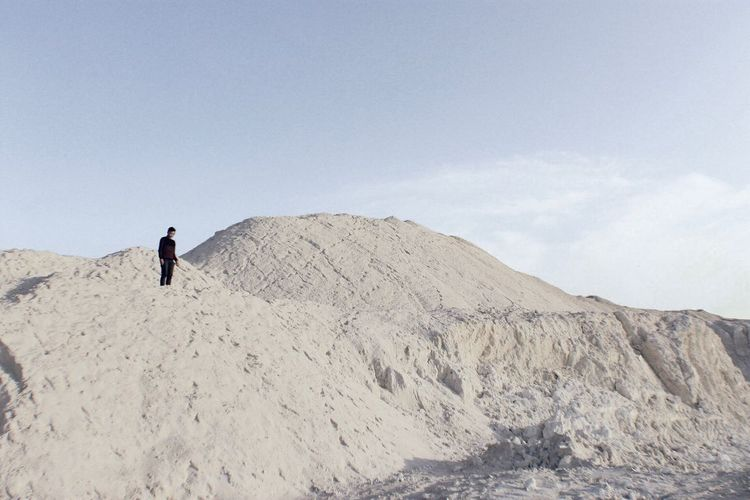 Low angle view of man standing on mountain at desert against sky
