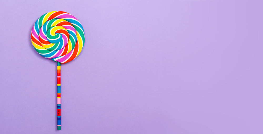 Close-up of multi colored candies against blue background