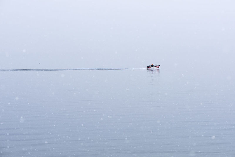 A lone fisherman cuts his small dinghy through the still waters of a lake in the snow. Hokkaido Isolated Japan Travel Winter Beauty In Nature Boat Commute Destination Focus Fisherman Fishing Fishing Boat Isolation Lake Minimalism Nature Nautical Vessel Outdoors Peaceful Snow Snowing Solitude Tranquil Scene Tranquility Water