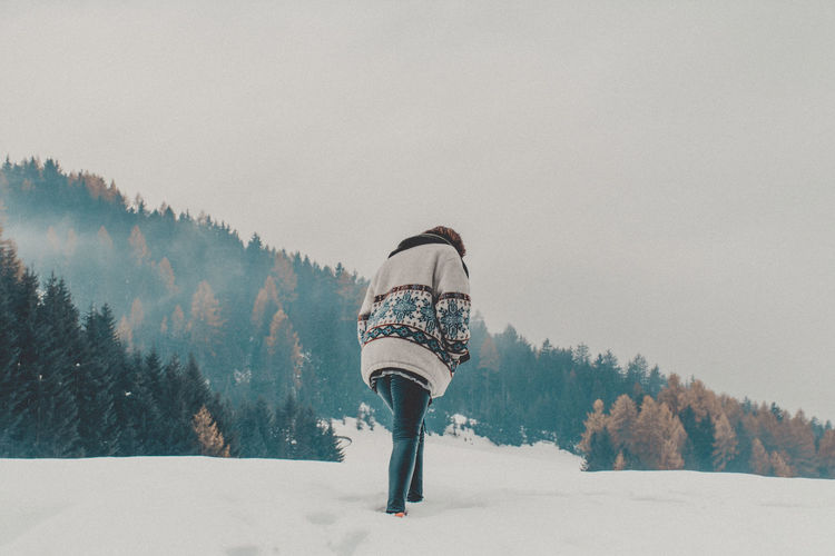 Rear view of person on snow covered field against sky