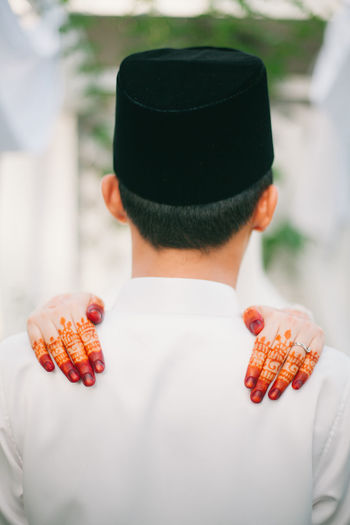 Rear view of man with woman hands on shoulders